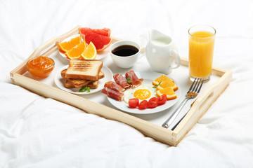 Tasty breakfast in bed on wooden tray