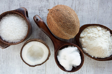Homemade coconut products on wooden table background. Coconut oil, coconut flour and shredded coconut