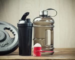 Fitness and sports concept with a  scoop of protein powder necessary nutrition for muscle recovery after an intensive workout, next to a protein shaker