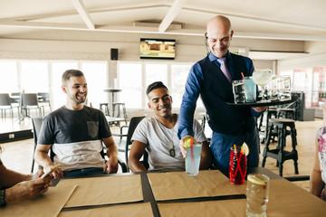Waiter serving drinks on table