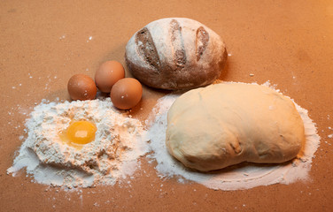 Round bread, three eggs, dough and an egg yolk surrounded by flour