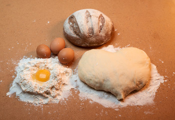 Dough in the shape of a heart, round bread, three eggs, and the yolk surrounded by flour
