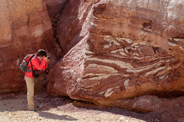 Female photographer taking picture of red sandstone rock in Eilat Mountains.