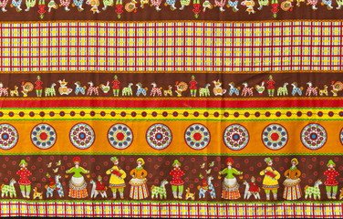 background: fragment of tablecloth in traditional Russian folk style with the images of Dymkovo toys, also known as the Vyatka toys or Kirov toys..