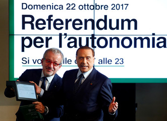 Forza Italia party leader Silvio Berlusconi shows the system to vote next to President of Lombardy Roberto Maroni during a news conference about the Lombardy autonomy referendums, in Milan