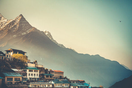 Sunrise view of Namche Bazaar village and Thamserku mountain, Khumbu valley, Nepal. Trekking route to Everest Base Camp, Himalayas. Travel background. Beautiful nature landscape. Retro vintage toning