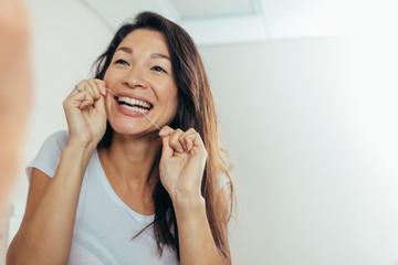 Reflection of woman using dental floss