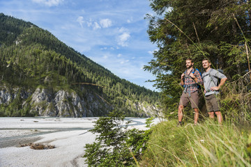 Germany, Bavaria, two young hikers with backpacks looking at view