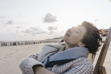 Woman relaxing in deckchair on the beach