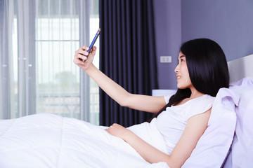 woman taking selfie on bed in bedroom