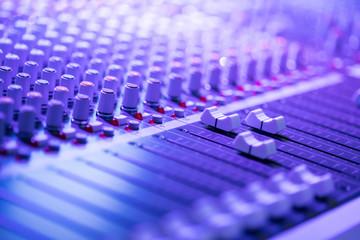 Mischpult in Nachtclub, Schalter und Regler, farbiges lila Licht