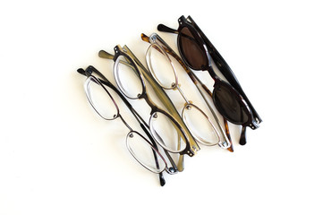 3 pairs of eyeglasses and a pair of sunglasses in a row isolated on white