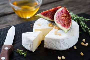 White cheese brie or camembert, figs, honey and nuts on dark cutting board. Closeup view