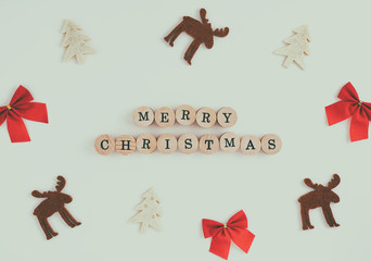 Christmas frame postcard from Christmas figures of Christmas tree, deer and red bow on a white background with an inscription of a Merry Christmas, on wooden round figures