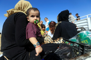 A displaced woman rides in a truck with her children as they head back to her home in Hawija, on the outskirts of Kirkuk