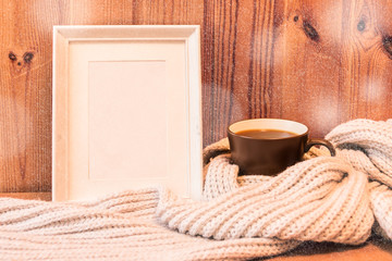 Vertical empty white wooden frame and mug with coffee wrapped in gray woolen scarf