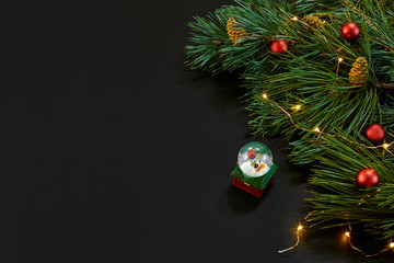 Christmas. Xmas toys and spruce branch on black background top view. Copy space.