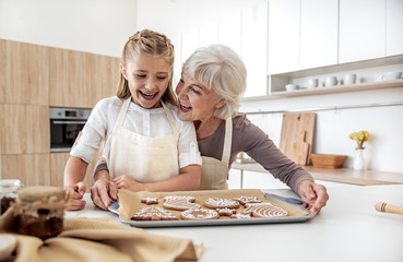 Joyful granny and child are satisfied with self-made pastry