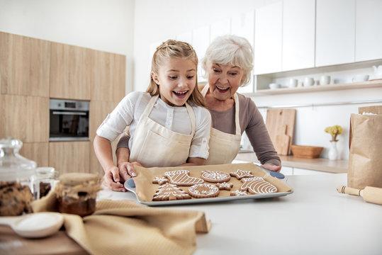 Happy senior woman enjoying baking process with her granddaughter