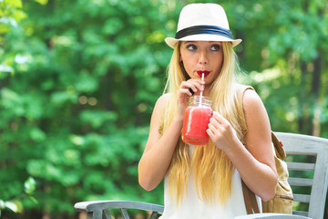 Young woman drinking a smoothie outside on a beautiful summer day