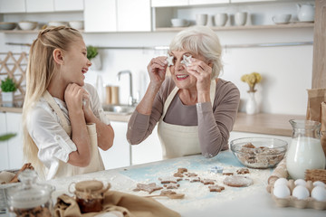 Happy granny rejoicing her granddaughter in kitchen