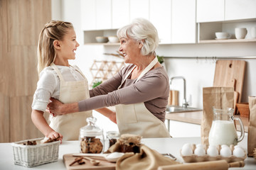 Cheerful girl entertaining with grandmother in kitchen