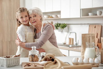 Joyful old woman and granddaughter are ready to cook together