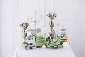 A table decorated with cake, eclairs, flowers and candles