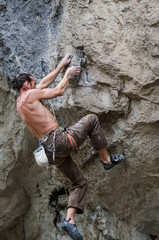 Muscular male climber holding with his hands on small rock grips