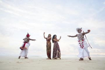 Tourists taking pictures of Kandyan Dancers on beach. Sri Lanka.