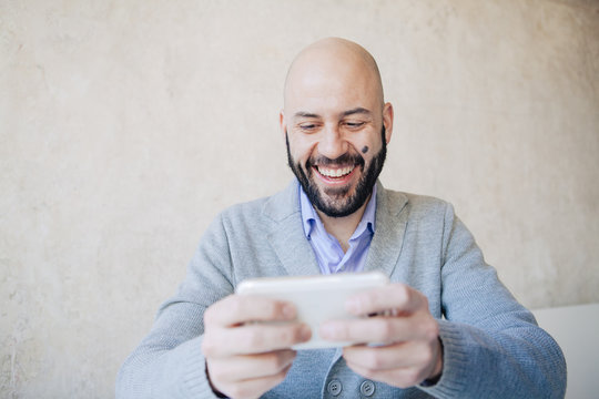 Smiling man reading text message