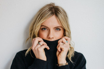 Young blonde female wearing dark sweater in front of white wall