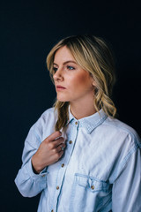Young blonde female woman on dark black blue wall wearing denim
