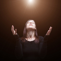 Mourning woman praying, with arms outstretched in worship to god, illuminated by a celestial or divine light. Concept for religion, faith, prayer, grief, mourn, pain, depression.