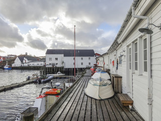 Different types of boats in a small harbor in Norway on a rainy day