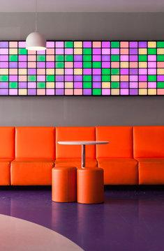 Designed minimalist orange interior with colorfull animated screen inside dico club.