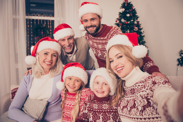Portrait of six cheerful multi generation relatives bonding on couch, married couple, excited siblings, grandad, granny, in traditional x mas costumes, pine firtree, home, happiness, love