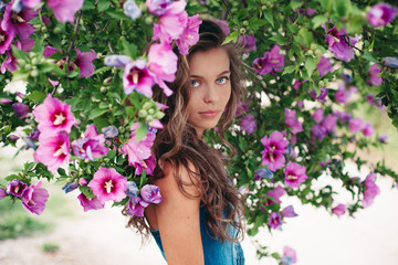 Spring portrait of beautiful girl around purple flowers bush