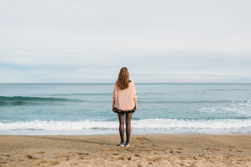 Standing woman looking at the sea
