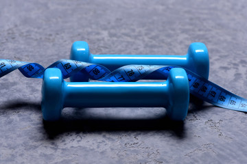 Pair of barbells and twisted measure tape, close up