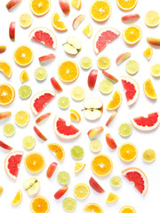 Food pattern of fresh fruit in a cut. Oranges, grapefruit, lemons, bananas, apples tangerines slices. Top view, flat lay. Citrus fruits  background, wallpaper.