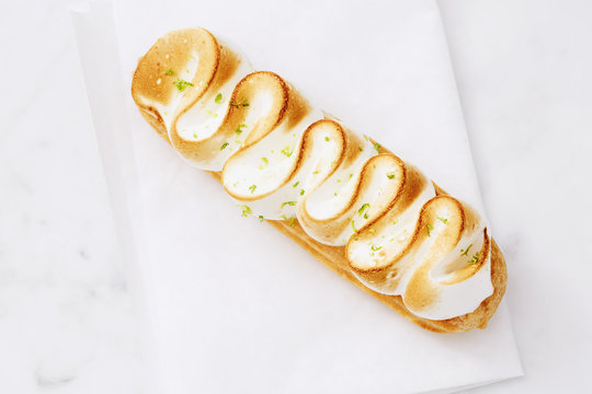 Eclair with lime cream and meringueб horizontal shot, from ahead