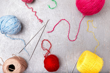 Multicolor knitting ball and needles on grey background. Top view. Copy space. Knitting yarn.
