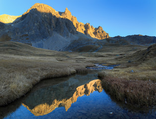 Fotomurales - Mountain peaks refelcted in a small stream during an autumn sunset.