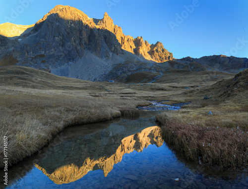 Fotomurales Mountain peaks refelcted in a small stream during an autumn sunset.