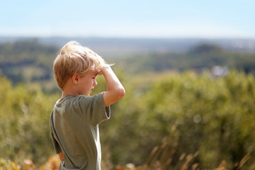 Little Boy Outside on Hike Looking out over Trees on Bluff