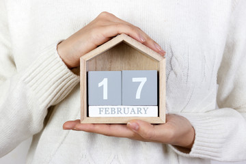 February 17 in the calendar. the girl is holding a wooden calendar. Random Acts of Kindness Day