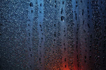 Raindrops on sweaty window with red tint
