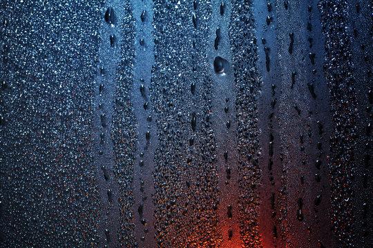 Raindrops on sweaty window with red tint
