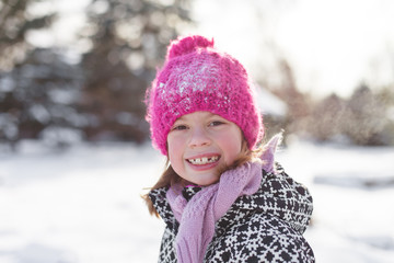 Happy smiling young girl playing outside in winter